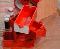 Freshly painted red wooden boxes and paint cans view from above. Freshly painted red wooden boxes and three paint cans view from above royalty free stock photo