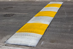 Freshly painted speed bump for slowing traffic near school. Selective focus Royalty Free Stock Images