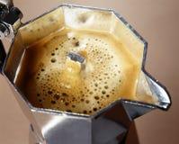 Freshly percolated coffee. Closeup high angle view of frothy freshly percolated espresso coffee in a stovetop moka espresso pot Royalty Free Stock Photography