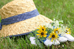 Freshly Picked. Flowers on a pair of gardening gloves with a straw hat in the background.  Gardening concept Royalty Free Stock Photo