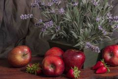 Freshly picked apples. Freshly picked flowers surrounded by a planter of freshly picked apples and strawberries set on the supper table ready to be enjoyed by Stock Image