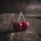 Freshly picked cherries on dark wooden table Royalty Free Stock Photo