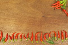 Freshly picked chili peppers on a wooden table. Preparation for the domestic processing of a crop. Stock Photos