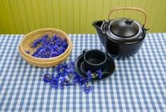 Freshly picked cornflower on basket clay tea set Royalty Free Stock Photography