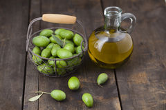 Freshly picked green olives and olive oil in jar on wooden table Royalty Free Stock Photography