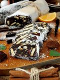Chocolate salami. Dessert made of biscuits, chocolate and nuts. Is sliced on a wooden board and covered with sugar powder Royalty Free Stock Images