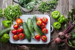 Freshly picked heirloom tomatoes, zucchini, beets, kale, peppers, cilantro and oregano on an old barn wood background stock photography