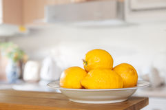 Freshly Picked Lemons. Fresh lemons in bowl sitting on countertop of kitchen, selective focus on front lemon with shallow dof Stock Photo