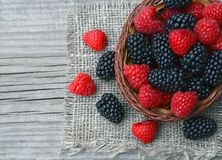 Freshly picked organic blackberries and raspberries in a basket on old wooden table. Healthy eating,vegan food or diet concept.Selective focus Stock Image