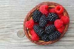 Freshly picked organic blackberries and raspberries in a basket on old wooden table. Healthy eating,vegan food or diet concept.Selective focus Stock Photo