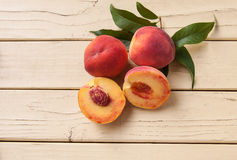 Freshly picked organic peaches on a yellow table Royalty Free Stock Photography