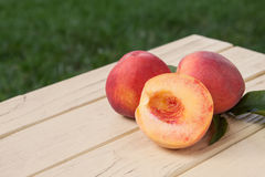 Freshly picked organic peaches on a yellow table Royalty Free Stock Images