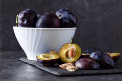 Freshly picked organic plums in bowl on table. Background Stock Photo
