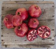 Freshly picked pomegranates displayed on weathered wood Royalty Free Stock Photo