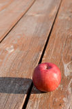Freshly picked red apple on weathered picnic table Royalty Free Stock Photography