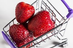 Freshly picked strawberries in shopping cart, close up, vitamin concept stock image