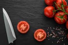 Freshly picked tomatoes on dark stone Stock Image