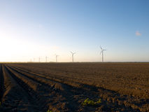 Freshly ploughed field with wind turbines at sunset Stock Images