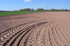 Freshly plowed earth on farm field. Freshly plowed earth in rural area on sunny summer day Stock Photos