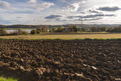 Freshly plowed fields. Farmhouse in the background Stock Images