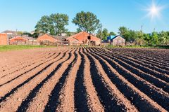 Plowing field and farm. Freshly plowing field and farm under blue sky Royalty Free Stock Image