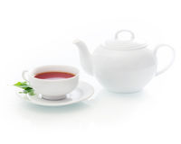 Freshly poured cup of hot tea with a teapot Royalty Free Stock Photos