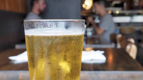 Freshly poured glass of light lager beer bubbling at top of glass at a restaurant with people dining stock footage