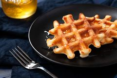 Freshly prepared belgian waffles with honey or maple syrup royalty free stock photography