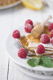 Freshly prepared crepes with raspberries royalty free stock photo