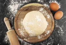 Freshly prepared dough on a wooden board. Rolling pin and egg Stock Photos