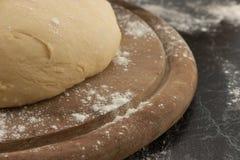 Freshly prepared dough on a wooden board. Selective focus Stock Photos