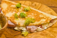 Breakfast quesadilla. Freshly prepared, homemade breakfast quesadilla toasted and filled with sliced ham and cheese and topped with guacamole on a round, wood royalty free stock images