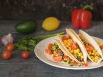 Freshly prepared Mexican tacos on a plate on a dark table with vegetables. Freshly prepared Mexican tacos on a plate on a rustic table. Tacos, corn, ground beef Royalty Free Stock Images