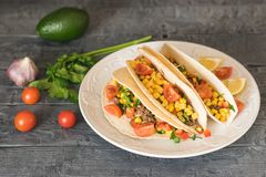 Freshly prepared Mexican tacos on a plate and avocado on a dark table with vegetables. Freshly prepared Mexican tacos on a plate on a rustic table. Tacos, corn Royalty Free Stock Photos