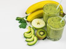 A freshly prepared smoothie of avocado, banana, orange, lemon and kiwi on a white wooden table. Diet vegetarian food. Raw foods. Stock Images