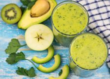 Two glass cups with a smoothie of avocado, banana, kiwi and herbs on a blue vintage table. Diet vegetarian food. Stock Images