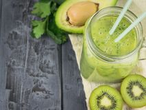 A freshly prepared smoothie of avocado, banana, orange, lemon and kiwi on a wooden table. Diet vegetarian food. Raw Stock Photography