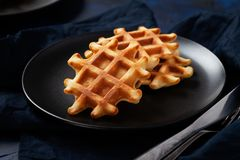 Freshly prepared sugary belgian waffles on black plate on dark blue background stock image