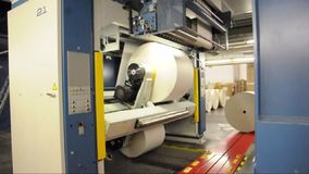 Freshly printed daily newspapers are transported on a conveyor belt in a printing plant stock footage