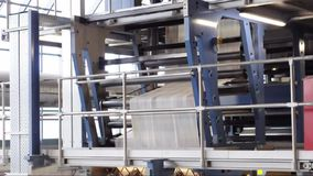 Freshly printed daily newspapers are transported on a conveyor belt in a printing plant stock video footage