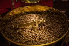 Freshly roasted aromatic coffee beans in a modern coffee roasting machine. royalty free stock photos