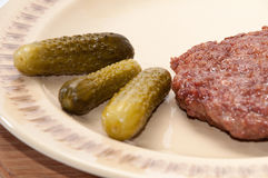 Freshly roasted burger and pickles served on a plate Royalty Free Stock Photo