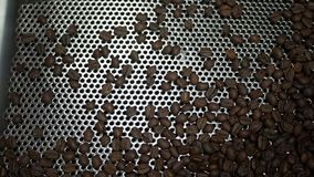 Freshly roasted coffee beans falling into a spinning cooler stock video