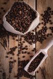 Coffee beans in jute sack and scoop on wooden background, top view stock photos