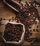 Coffee beans in jute sack and scoop on wooden background, top view royalty free stock photos