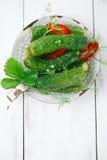 Freshly-salted cucumbers on vintage enamel sieve Stock Photo