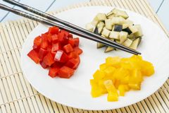 Freshly sliced bell peppers and eggplant on bamboo mat. Vegetarian food in oriental style. Healthy food concept.  stock photo