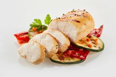 Freshly sliced cooked chicken with salad. Freshly sliced cooked chicken with courgettees and herbs on studio background stock images