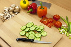 Freshly sliced English cucumber on a wooden chopping board. Freshly sliced English cucumber laying on a wooden chopping board with a knife aside some cut mixed Stock Photos