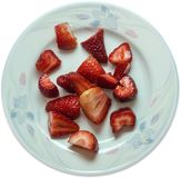Freshly sliced juicy strawberries. On a blue tinted plate isolated on white background Stock Image